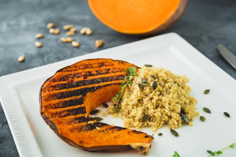 Baked pumpkin with sprouted millet and pumpkin grains on the dark table. Vegetarian food. Flat lay. Top view. Baked pumpkin with sprouted millet and pumpkin royalty free stock images