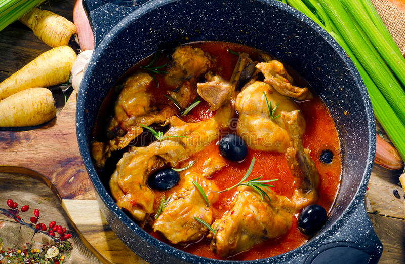 Baked rabbit in tomato sauce with black olives and fresh herbs. Top view stock photography