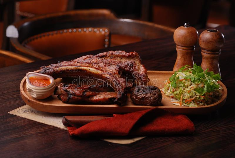 Baked ribs with suace and vagetables. Food photo for restaurant menu royalty free stock image