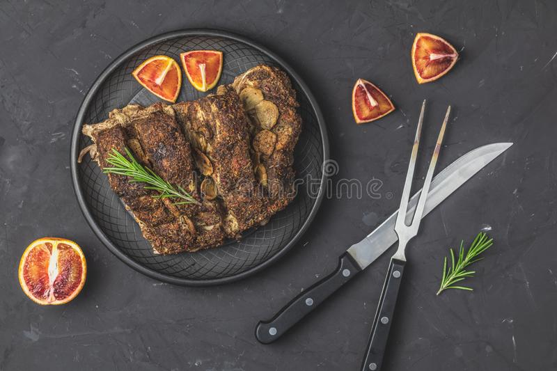 Baked roast pork meat in black ceramic plate, dark concrete surface. Delicious baked roast pork meat in black ceramic plate with garlic and spices. Dish for royalty free stock photography