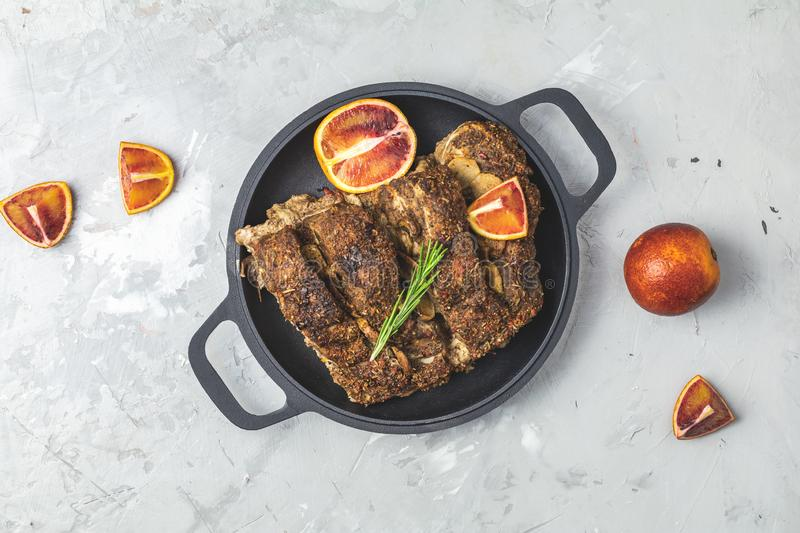 Baked roast pork meat in black frying pan. Delicious baked roast pork meat in black frying pan with garlic, and spices. Dish for dinner. Top view, flat lay, copy stock image