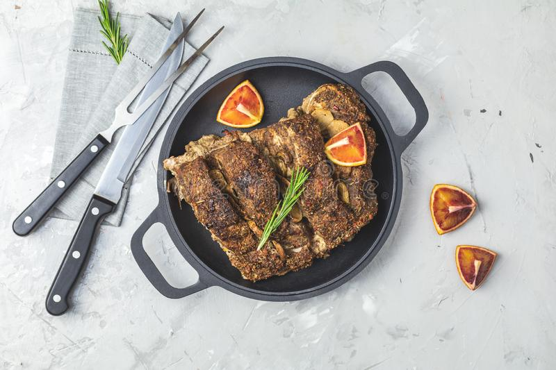 Baked roast pork meat in black frying pan. Delicious baked roast pork meat in black frying pan with garlic, and spices. Dish for dinner. Top view, flat lay, copy royalty free stock photo