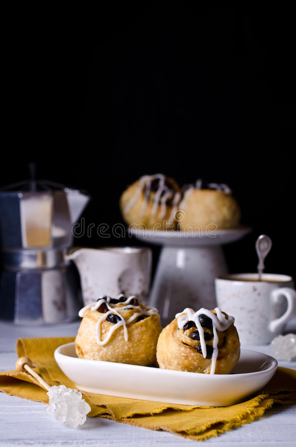 Baked rolls with raisins. And icing. Selective focus stock image