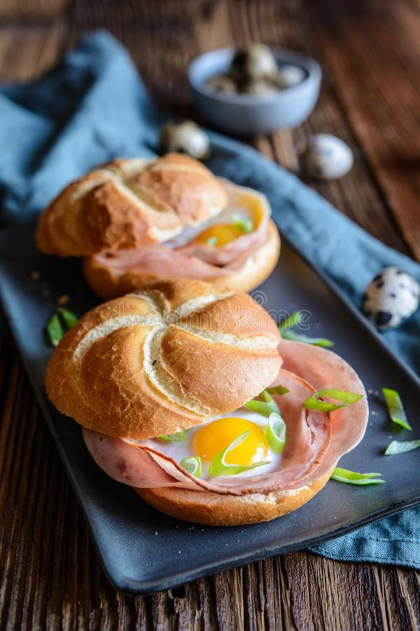 Baked rolls stuffed with ham, quail eggs and green onion royalty free stock image