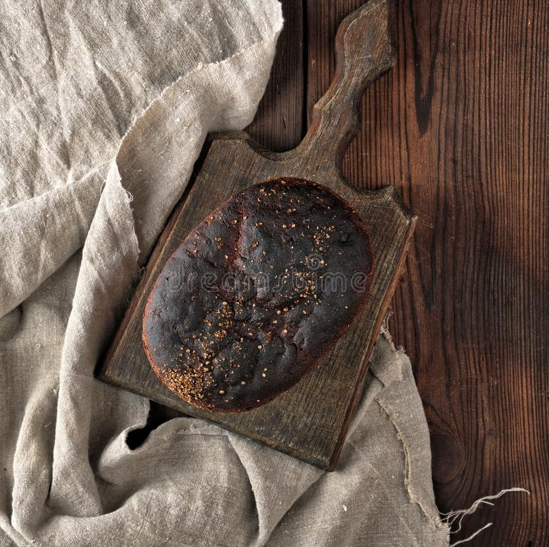 baked rye bread on a gray linen napkin, brown wooden table stock photo