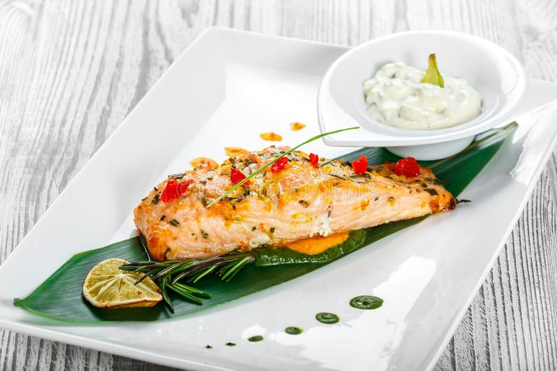Baked salmon with cheese sauce, rosemary and lemon on wooden background. Hot fish dish. Top view stock images