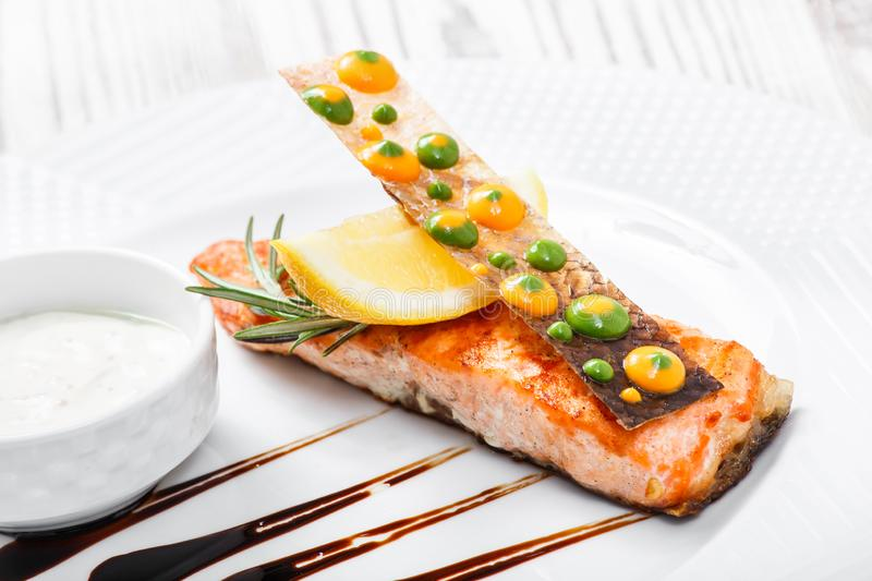 Baked salmon with cheese sauce, rosemary and lemon on wooden background close up. Hot fish dish stock image
