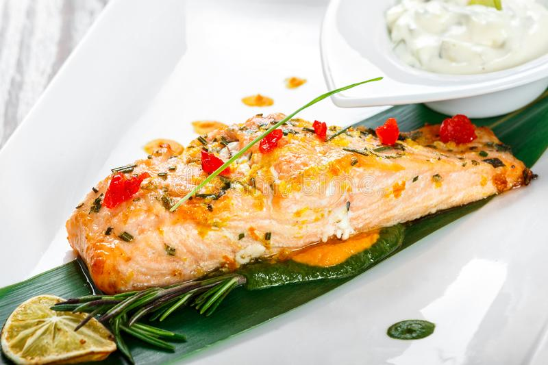 Baked salmon with cheese sauce, rosemary and lemon on wooden background. Hot fish dish. Top view royalty free stock image