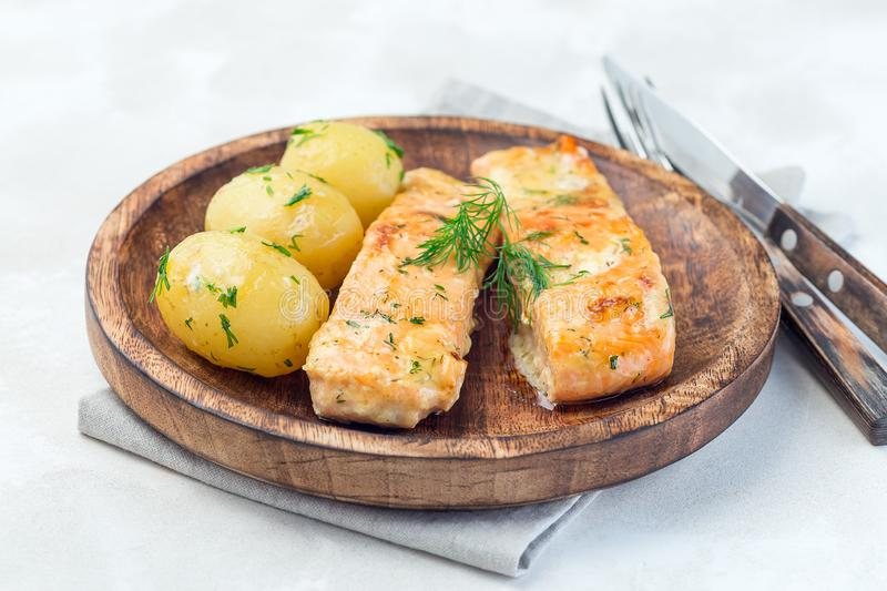 Baked salmon in creamy sauce with young boiled  potato topped with melted butter and chopped dill on a wooden plate, horizontal. Baked salmon in creamy sauce stock image