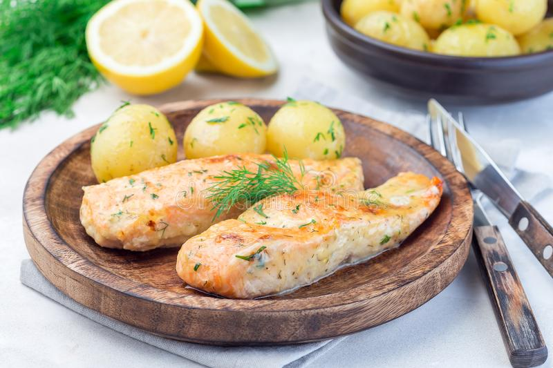 Baked salmon in creamy sauce with young boiled  potato topped with melted butter and chopped dill on wooden plate, horizontal. Baked salmon in creamy sauce with stock photography