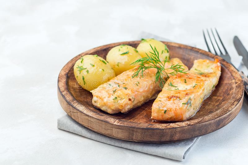 Baked salmon in creamy sauce with young boiled  potato topped with melted butter and chopped dill on  wooden plate, horizontal,. Baked salmon in creamy sauce royalty free stock photography