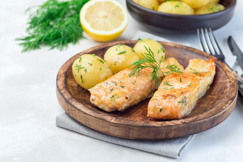 Baked salmon in creamy sauce with young boiled  potato topped with melted butter and chopped dill on wooden plate, horizontal,. Baked salmon in creamy sauce with stock images