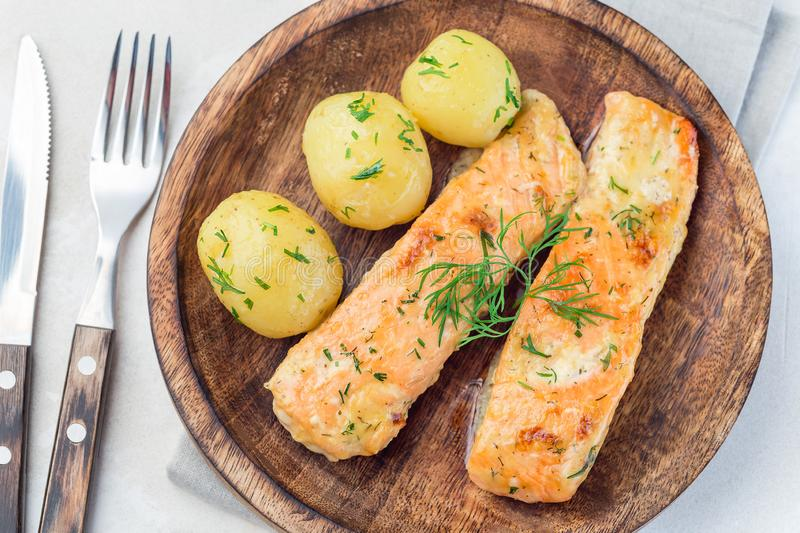 Baked salmon in creamy sauce with young boiled  potato topped with melted butter and chopped dill on a wooden plate, horizontal,. Baked salmon in creamy sauce stock image