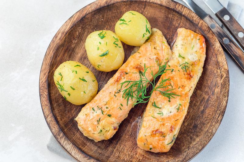 Baked salmon in creamy sauce with young boiled  potato topped with melted butter and chopped dill on  wooden plate, horizontal,. Baked salmon in creamy sauce stock photo