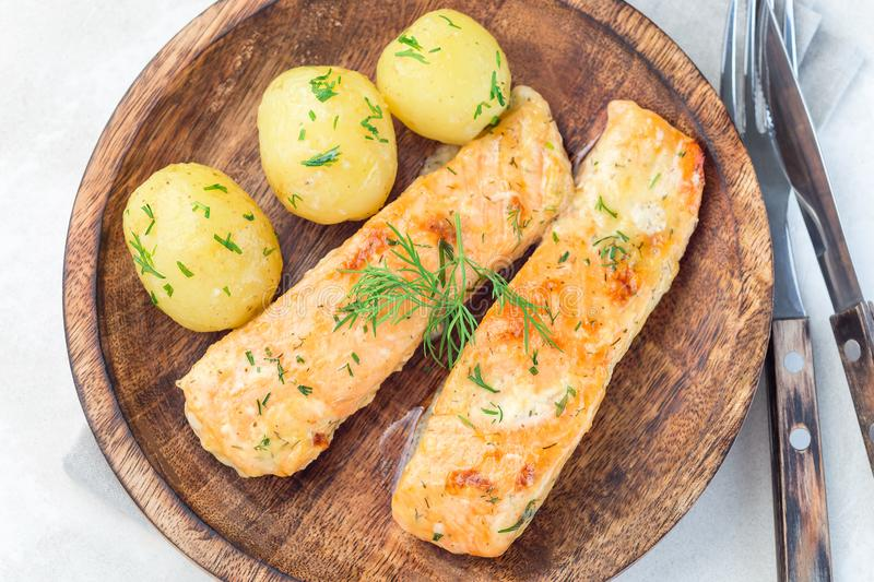 Baked salmon in creamy sauce with young boiled  potato topped with melted butter and chopped dill on  wooden plate, horizontal,. Baked salmon in creamy sauce royalty free stock images
