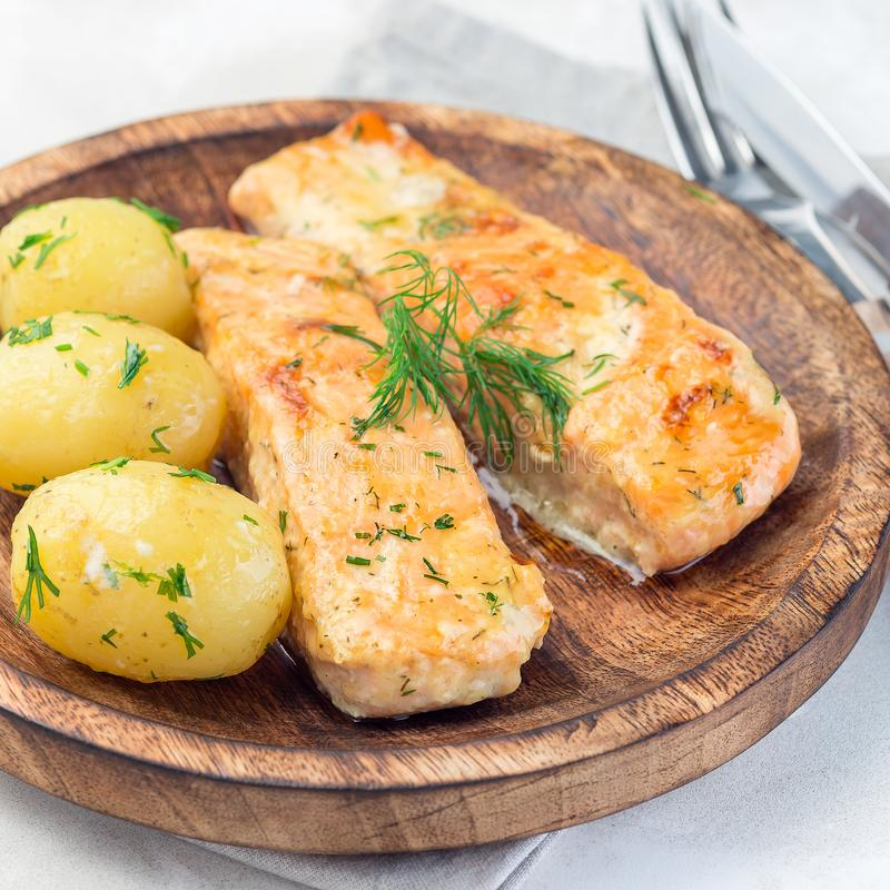 Baked salmon in creamy sauce with young boiled  potato topped with melted butter and chopped dill on  wooden plate, square format. Baked salmon in creamy sauce stock images