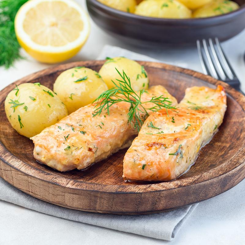 Baked salmon in creamy sauce with young boiled  potato topped with melted butter and chopped dill on  wooden plate, square format. Baked salmon in creamy sauce royalty free stock image