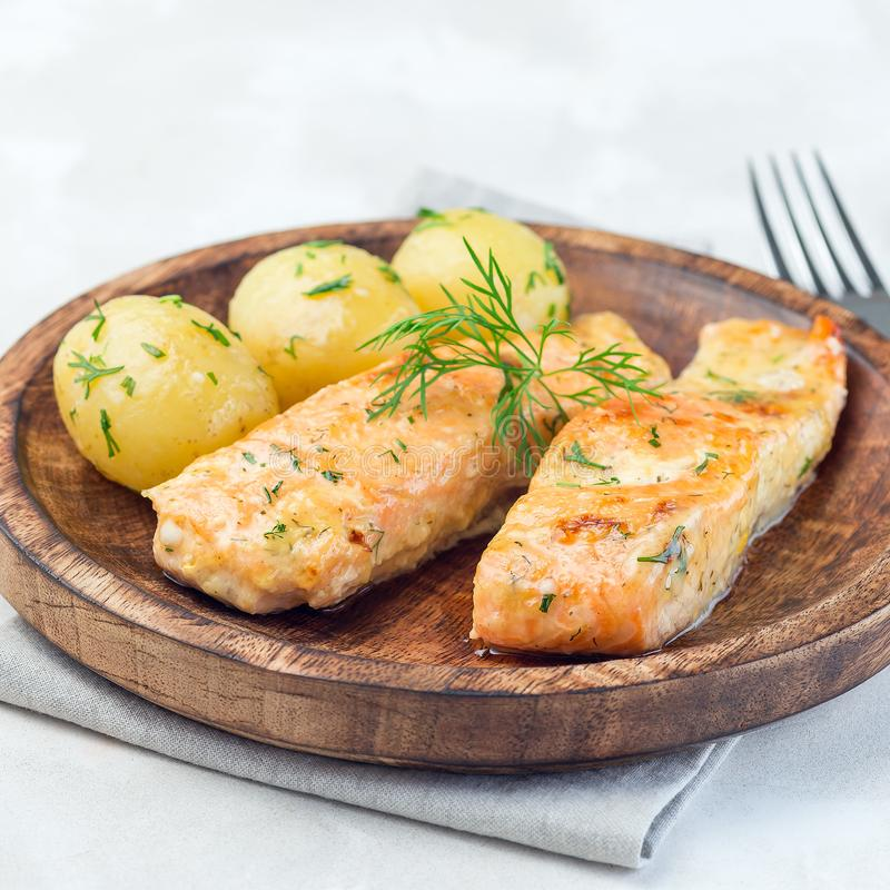 Baked salmon in creamy sauce with young boiled  potato topped with melted butter and chopped dill on a wooden plate, square format. Baked salmon in creamy sauce stock photo