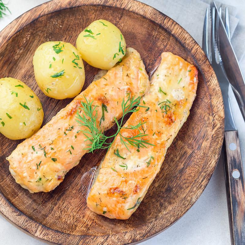 Baked salmon in creamy sauce with young boiled  potato topped with melted butter and chopped dill on wooden plate, top view,. Baked salmon in creamy sauce with stock photos