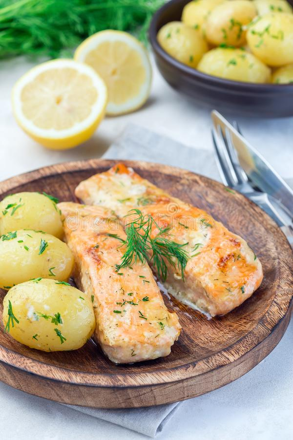 Baked salmon in creamy sauce with young boiled  potato topped with melted butter and chopped dill on wooden plate, vertical. Baked salmon in creamy sauce with stock image