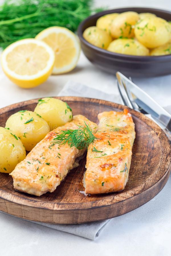 Baked salmon in creamy sauce with young boiled  potato topped with melted butter and chopped dill on  wooden plate, vertical. Baked salmon in creamy sauce with royalty free stock photos