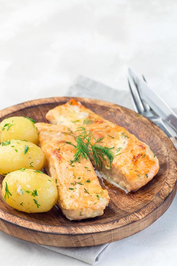 Baked salmon in creamy sauce with young boiled  potato topped with melted butter and chopped dill on wooden plate, vertical, copy. Baked salmon in creamy sauce stock images