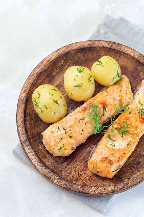 Baked salmon in creamy sauce with young boiled  potato topped with melted butter and chopped dill on  wooden plate, vertical, top stock photography