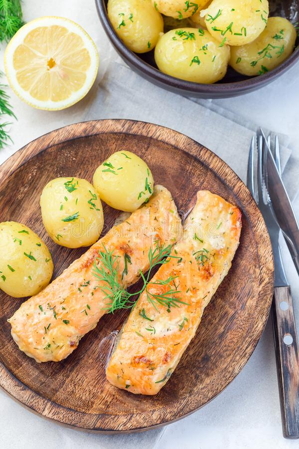 Baked salmon in creamy sauce with young boiled  potato topped with melted butter and chopped dill on  wooden plate, vertical, top. Baked salmon in creamy sauce stock photos