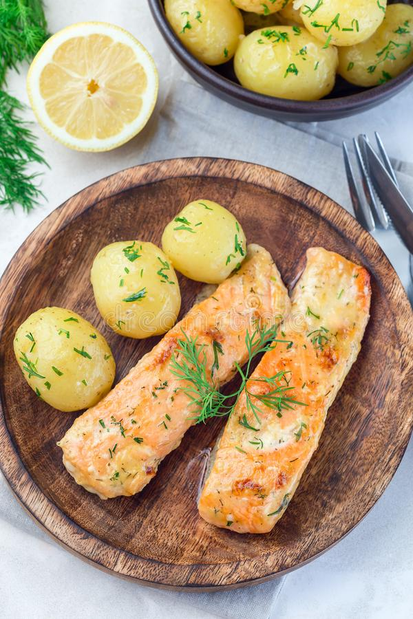 Baked salmon in creamy sauce with young boiled  potato topped with melted butter and chopped dill on wooden plate, vertical, top. Baked salmon in creamy sauce stock photo