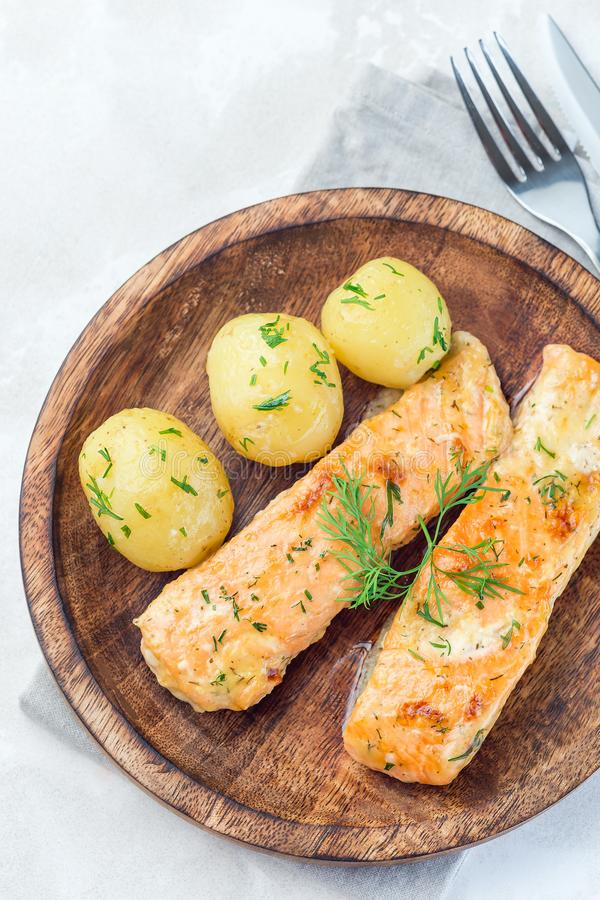 Baked salmon in creamy sauce with young boiled  potato topped with melted butter and chopped dill on a wooden plate, vertical, top. Baked salmon in creamy sauce stock image