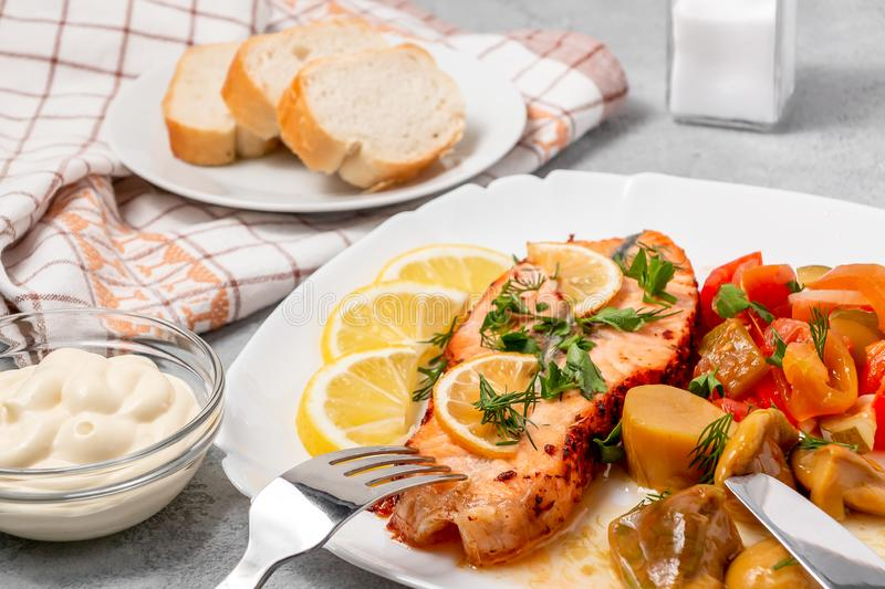 Baked salmon fillet medallion with salad of pickled vegetables and mushrooms on a white plate on a gray background stock photos