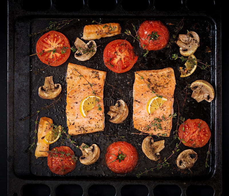 Baked salmon fish fillet with tomatoes, mushrooms and spices. Diet menu. Top view. Flat lay royalty free stock images