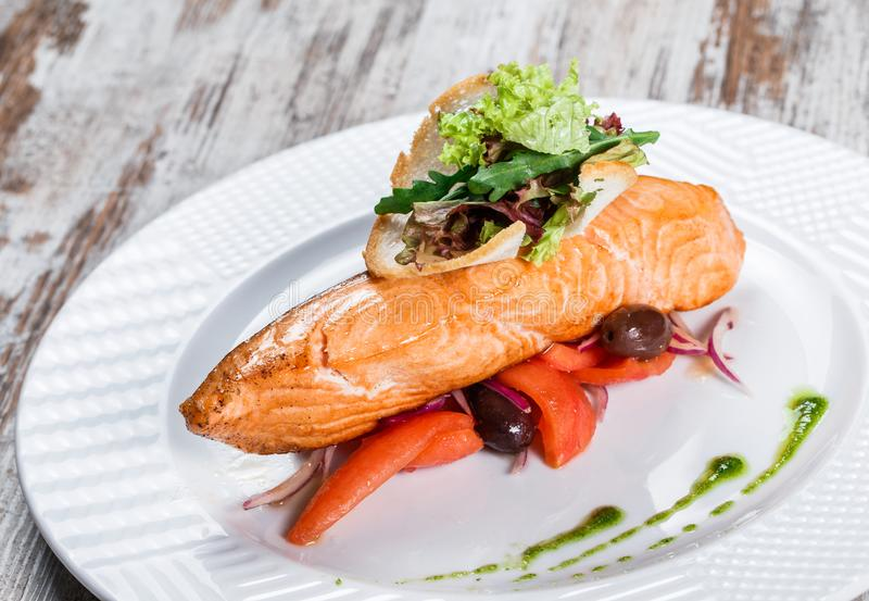 Baked salmon garnished with olives, greens, tomatoes on plate over wooden background. Hot fish dish.  stock photography