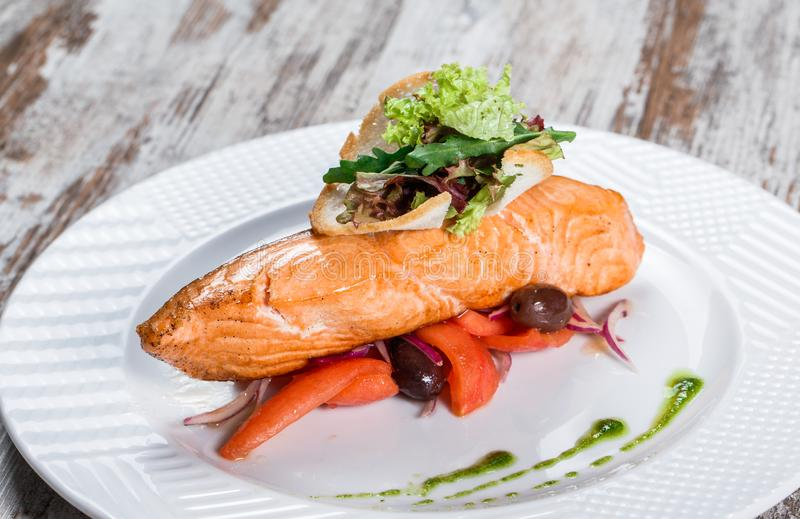 Baked salmon garnished with olives, greens, tomatoes on plate over wooden background. Hot fish dish.  stock images