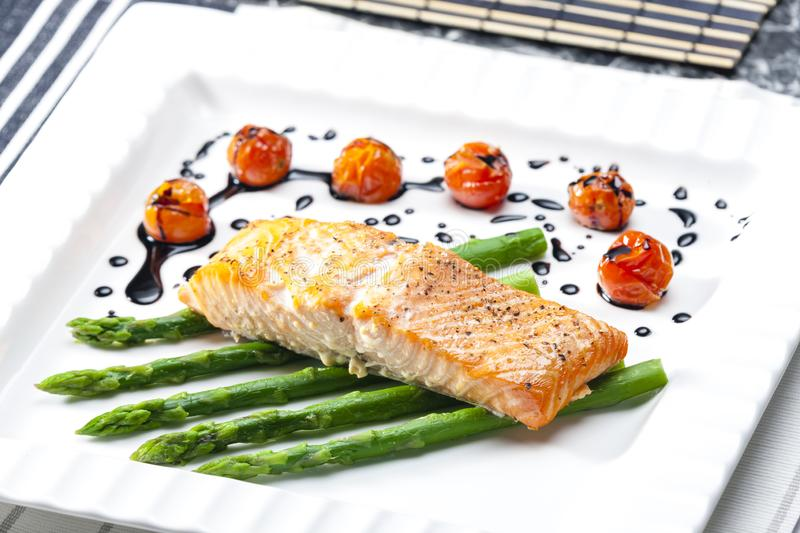 baked salmon with green asparagus and cherry tomatoes stock images