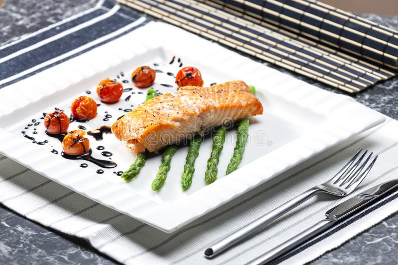 baked salmon with green asparagus and cherry tomatoes stock photo