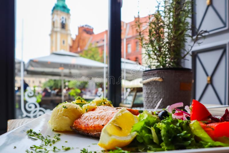 Baked salmon with mashed potatoes, lemon, tomatoes, red onions, olives and salad leaves on a background of historical buildings of. Torun, Poland. Restaurant stock images