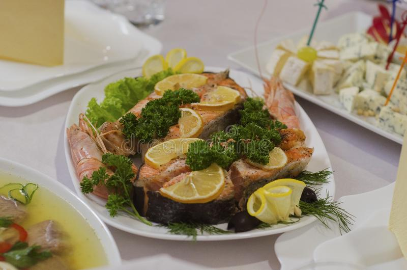 Baked salmon steak dish garnished with lemon parsley and shrimp 3 stock image
