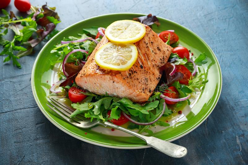Baked salmon steak with tomato, onion, mix of green leaves salad in a plate. healthy food royalty free stock photo