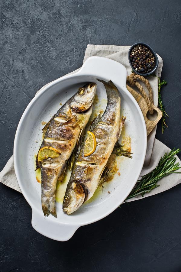 Baked sea bass in a baking dish. Black background, top view, space for text. stock photos