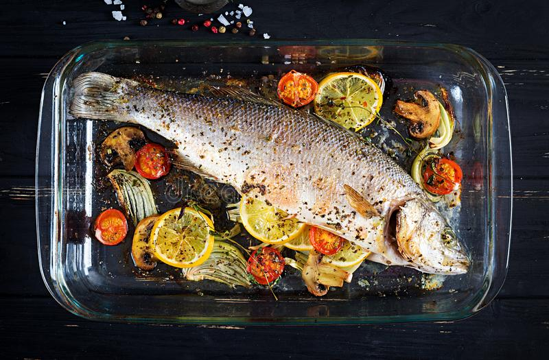 Baked sea bass in a baking dish with spices and vegetables royalty free stock image