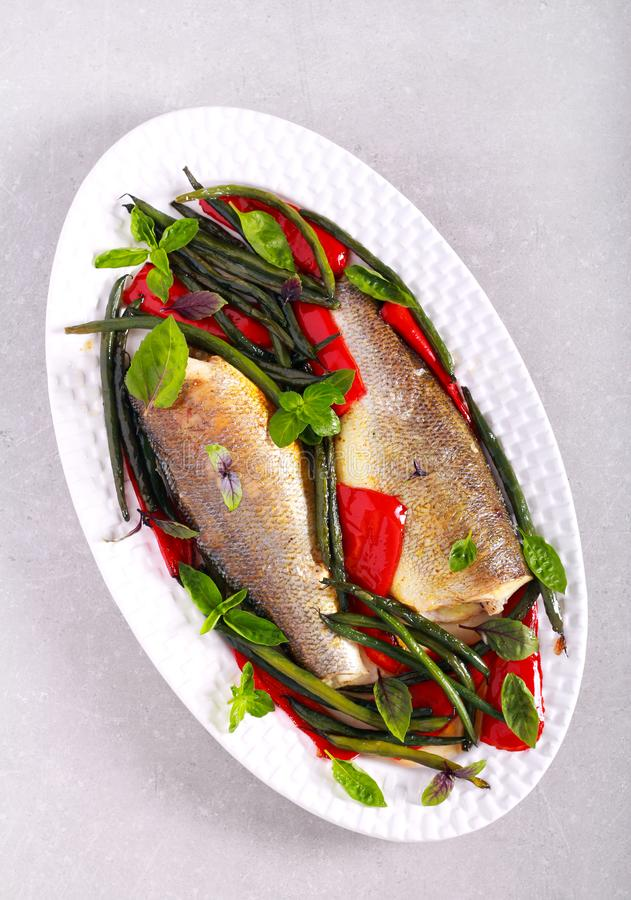 Baked sea bass fish. With red pepper and green beans royalty free stock photo