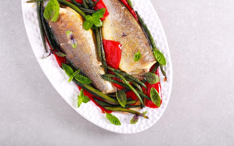 Baked sea bass fish. With red pepper and green beans stock photography