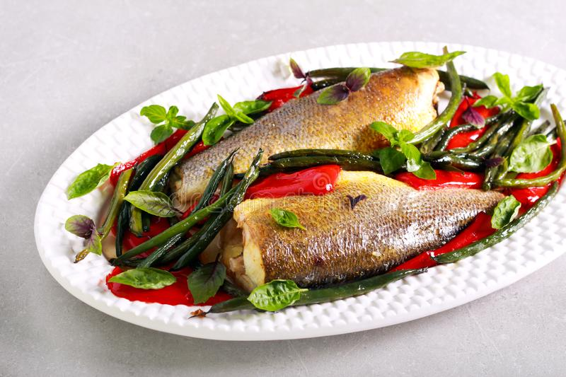 Baked sea bass fish. With red pepper and green beans stock image