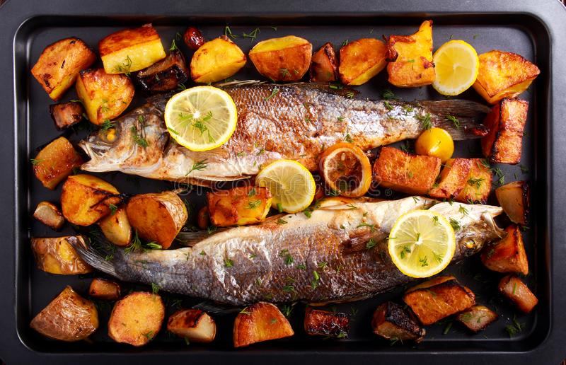 Baked sea bass fish and vegetables on black tin. Top view stock photo