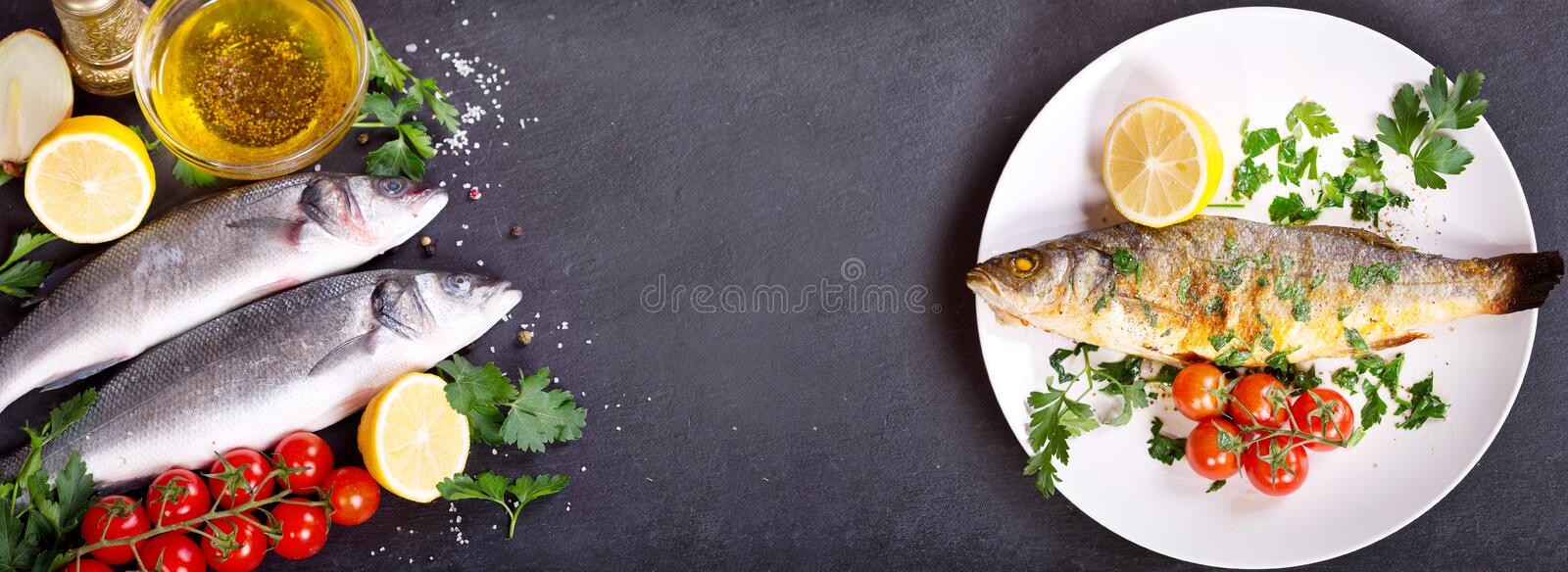 Baked sea bass and fresh fish with ingredients for cooking royalty free stock photography