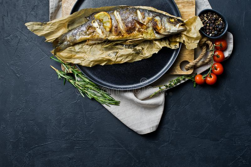 Baked sea bass on Kraft paper in a black plate. Black background, top view, space for text. stock images