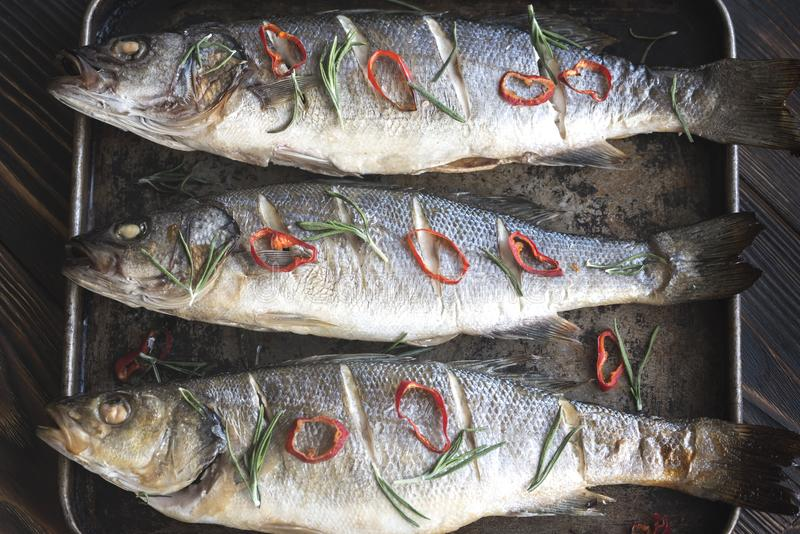 Baked sea bass with lime and chilli pepper royalty free stock images