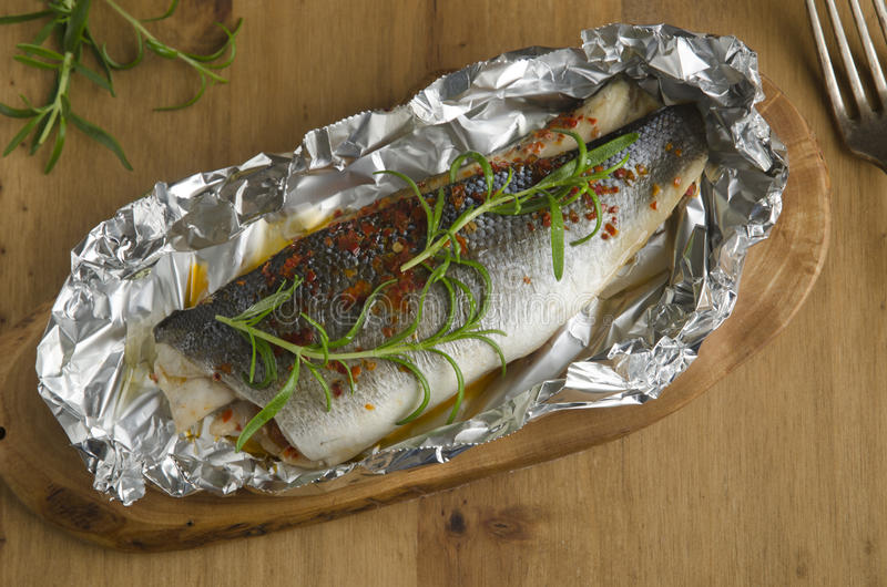 Baked sea bass. Stuffed with tomatoes and kalamata olives stock images