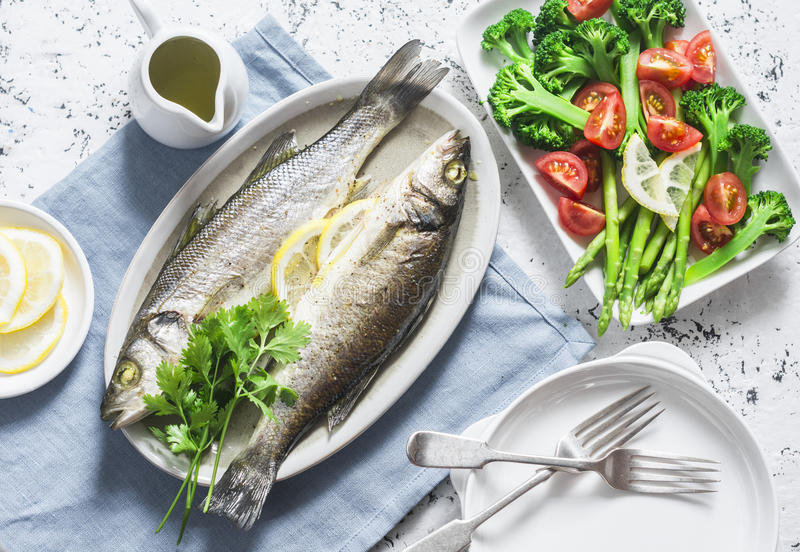 Baked sea bass and vegetables - broccoli, asparagus, tomatoes on a light background, top view. Healthy balanced meal. Concept royalty free stock photography